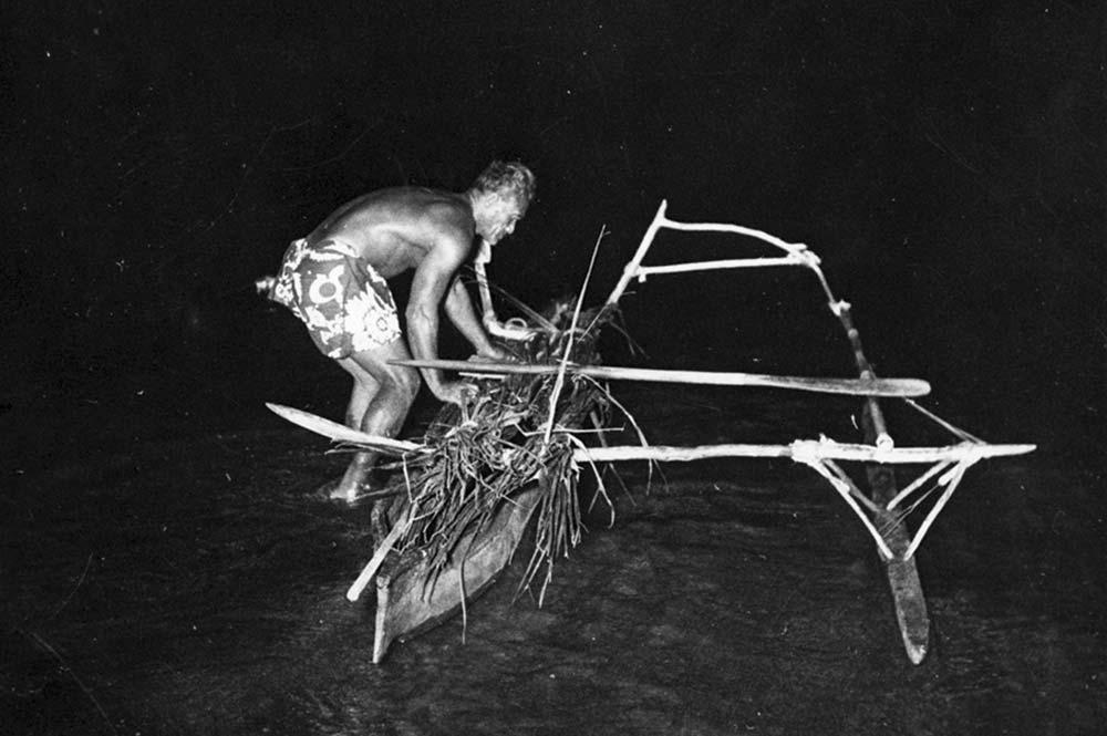 Pêcheur en pirogue de nuit. Defap