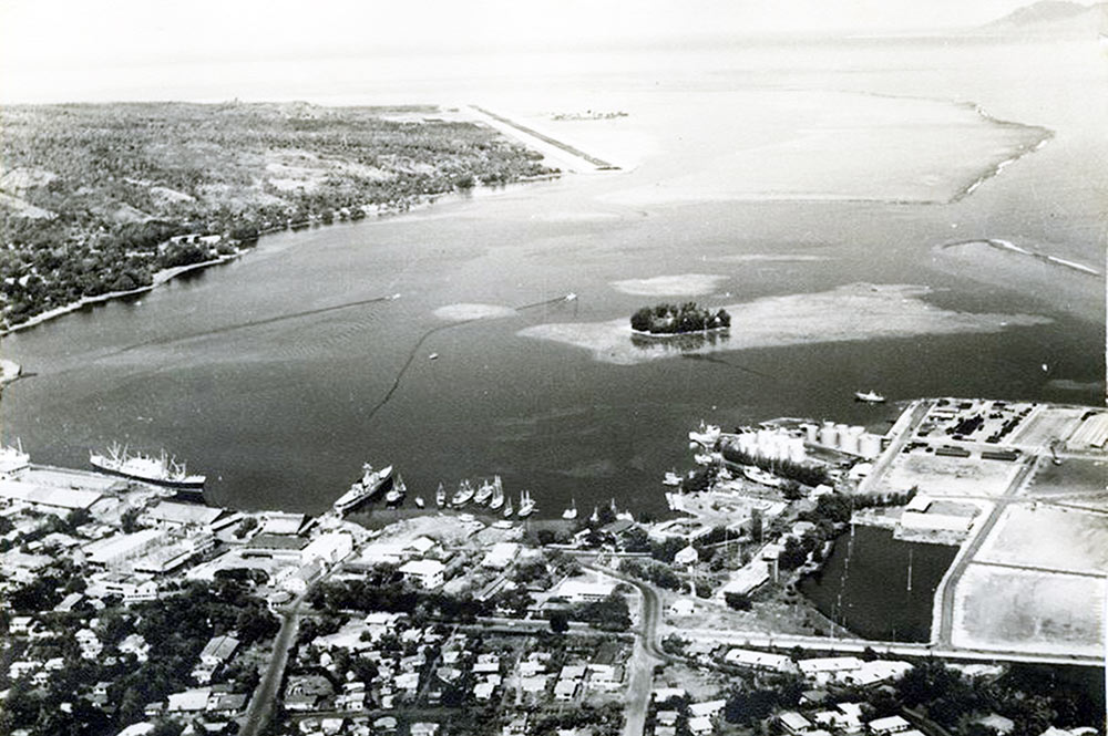 Vue aérienne du port de Papeete avec le petit îlot de Motu Uta vers 1950
